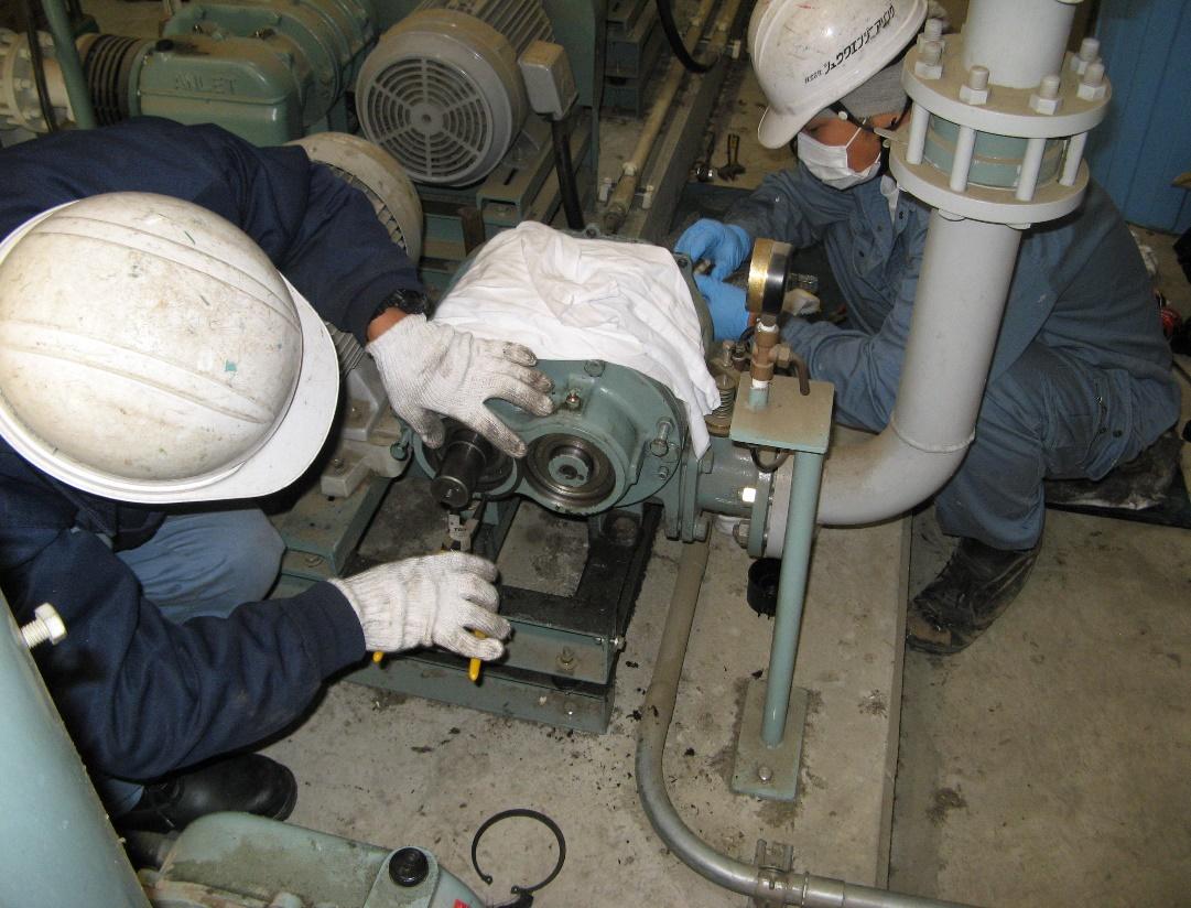 ころがり軸受を交換しているところの写真です。2人がかりで手に工具を持ち、作業を行っています。