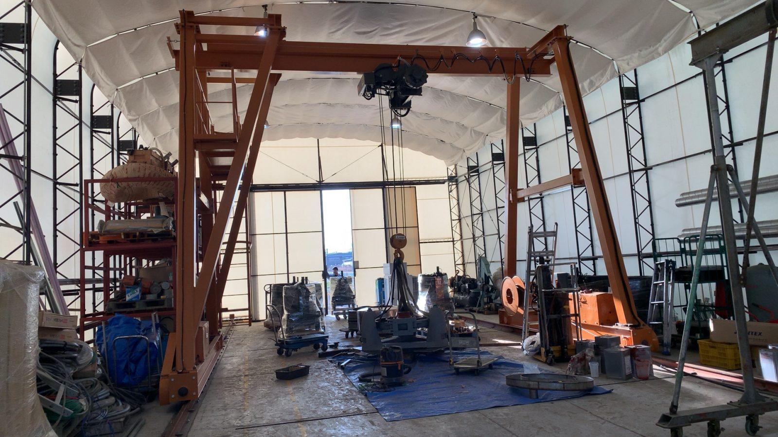脱水機をシュウワエンジニアリングの工場に搬入した際の写真です。大型クレーンで吊り上げ、工場内部に移動します。