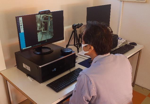 山梨本社で対応する技術者の写真です。モニターには現地の様子が映し出されて、現場の担当者に指示を出します。