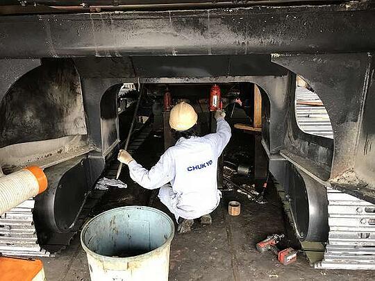 車体の下の潜り込んで点検・整備している写真です。